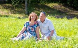 El hombre y la mujer se sientan en la hierba fotos de archivo libres de regalías