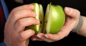 El hombre y la mujer se sostienen en manos con la manzana de las mitades Imagenes de archivo