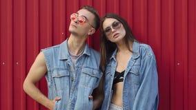 El hombre y la mujer se vistieron en estilo casual de la calle con las gafas de sol presentan antes de una pared roja almacen de metraje de vídeo