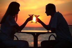 El hombre y la mujer tintinean los vidrios en puesta del sol afuera Imagen de archivo libre de regalías