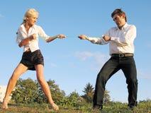 El hombre y la mujer tiran de una cuerda Imagen de archivo libre de regalías