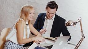El hombre y la mujer trabajan juntos en la oficina