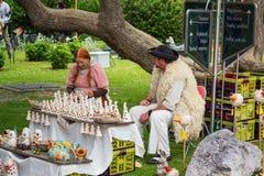 El hombre y la mujer, vestidos en trajes tradicionales del pastor, venden las estatuas de cerámica Imagen de archivo libre de regalías