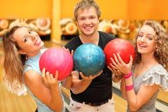 El hombre y las muchachas hicieron la fila de bolas en club del bowling Imagenes de archivo
