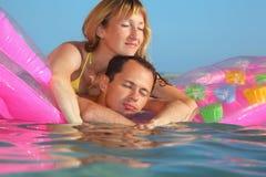 El hombre y las mujeres duermen en un colchón en piscina Imagenes de archivo