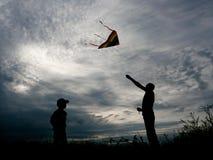 El hombre y el niño adultos lanzan una cometa contra una puesta del sol hermosa del verano Imágenes de archivo libres de regalías