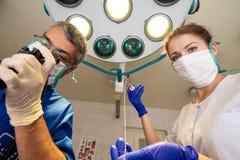 El hombre y una mujer en máscaras se colocan que se hacen frente y que sostienen los instrumentos médicos en sus manos imagenes de archivo
