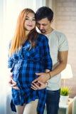 El hombre y una mujer joven embarazada están esperando a un niño en casa b imagen de archivo