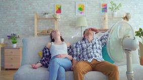 El hombre y una mujer que se sienta en un sofá con una fan eléctrica se están escapando del calor metrajes