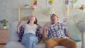 El hombre y una mujer que se sienta en un sof? con una fan el?ctrica se est?n escapando del calor MES lento almacen de metraje de vídeo