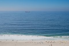 El horizonte nublado y la niebla sobre el mar agita, el fondo natural, buque de carga rojo en el horizonte, playa en el primero p fotografía de archivo