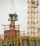 El hormigón colado de los trabajadores de construcción bajó de una grúa Imagenes de archivo
