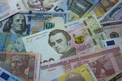 El hryvnia ucraniano, los billetes de dólar, los euros y el otro dinero Foto de archivo