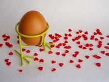 El huevo de Brown del color claro en una ayuda se prepara para el día de fiesta Pascua en un fondo blanco derramado con rojo bril foto de archivo libre de regalías