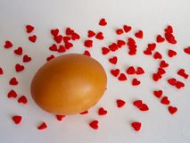 El huevo de Brown del color claro en una ayuda se prepara para el día de fiesta Pascua en un fondo blanco derramado con rojo bril fotos de archivo