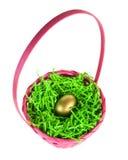 El huevo de oro nestled en una cesta rosada de pascua Fotografía de archivo