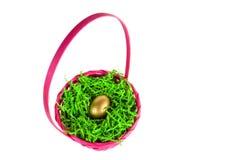 El huevo de oro nestled en una cesta rosada de pascua Imagen de archivo libre de regalías