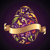 El huevo de Pascua con la cinta del estampado de plores y del oro marca con etiqueta Fotografía de archivo libre de regalías
