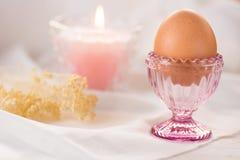 El huevo de Pascua en la taza cristalina rosada, fondo blanco de paño de lino, vela ardiente, ramo de primavera florece Fotografía de archivo