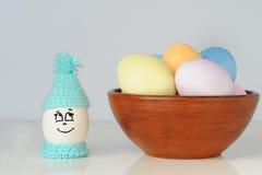 El huevo de Pascua mira un cuenco de huevos coloreados Imagenes de archivo