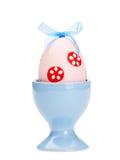 El huevo de Pascua rosado está en huevera azul fotos de archivo libres de regalías