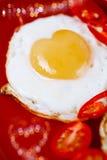 El huevo frito con el corazón forma las yemas de huevo y el bokeh en forma de corazón Imágenes de archivo libres de regalías