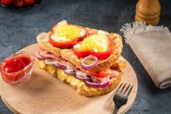 El huevo frito frió en rebanada de pimienta dulce y de bocadillo rojos con el jamón y las verduras estacionales en la placa blanc Foto de archivo libre de regalías