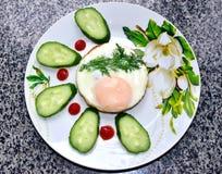 El huevo frito miente en una placa con los pepinos y se adorna con una rama del eneldo imagenes de archivo