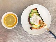 el huevo y el aguacate en tostada y el limón riegan Imágenes de archivo libres de regalías