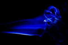 El humo azul abstracto remolina sobre fondo negro Fotografía de archivo
