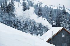 El humo de la chimenea de una casa en una estación de esquí en invierno Fotografía de archivo