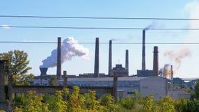 El humo de las chimeneas de la planta metalúrgica industrial sube en la atmósfera cerca de la ciudad almacen de video