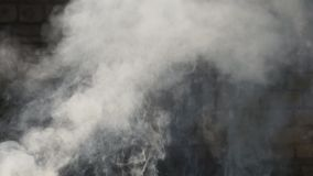 El humo sale de los escombros como consecuencia de la demolición del tsunami del ataque del cohete del terremoto almacen de metraje de vídeo