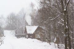 El humo viene de la chimenea de una casa rural en nevadas fuertes nevosas del bosque en día de invierno Imagen de archivo libre de regalías