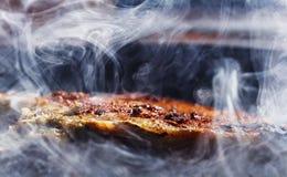 El humo y el vapor suben de un filete del cerdo en la cacerola de la parrilla Foto de archivo