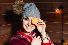El humor del invierno Mujer de pelo oscuro hermosa joven que sonríe en ropa y casquillo con las mandarinas en fondo de madera Foto de archivo libre de regalías