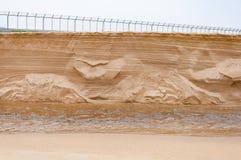 El hundimiento de la duna de arena abajo a un pequeño canal reveló textura dentro Foto de archivo libre de regalías
