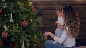 El idilio de la familia, madre joven con la hija adorna el árbol del Año Nuevo junto en el sitio en víspera de Navidad almacen de metraje de vídeo