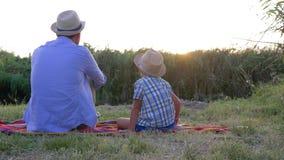 El idilio de la familia, papá con el hijo en sombreros de paja se basa sobre la manta en el fondo de la puesta del sol en rural e almacen de metraje de vídeo