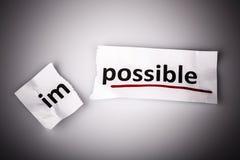 El imposible de la palabra cambiado a posible en el papel rasgado Imagen de archivo