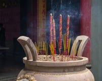 El incienso ardiente se pega en templo en la ciudad de Ho Chi Minh Imagen de archivo libre de regalías