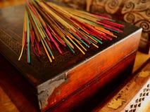 El incienso coloreado se pega en una caja de madera vieja Fotografía de archivo libre de regalías