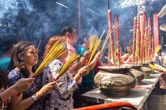 El incienso de las manos de la mujer ruega la primavera de la hornilla de incienso del templo Imágenes de archivo libres de regalías