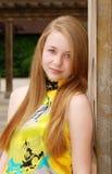El inclinarse adolescente femenino rubio en un pilar de madera Imagen de archivo