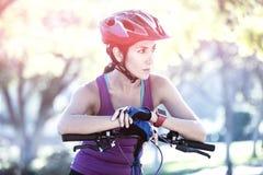 El inclinarse atlético femenino en la bicicleta en campo Foto de archivo libre de regalías