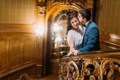 El inclinarse de abarcamiento y que se besa de los pares encantadores del recién casado en la barandilla en las escaleras antigua Fotos de archivo