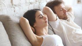 El inclinarse de reclinación relajado del hombre joven y de la mujer en el sofá cómodo almacen de metraje de vídeo