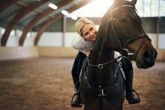 El inclinarse femenino rubio sonriente en negro a caballo Imagen de archivo libre de regalías