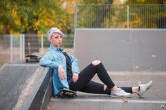 El inclinarse que se sienta de la muchacha en una rampa en un parque del patín Fotografía de archivo libre de regalías