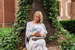 El inclinarse que se sienta hermoso de la mujer joven en un árbol en el medio de la hiedra Imágenes de archivo libres de regalías